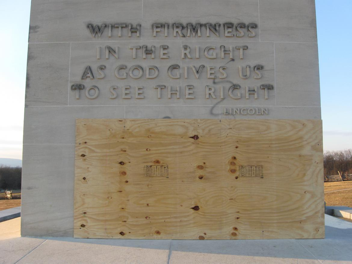 Large plywood covering vandalism on the Peace Light Memorial